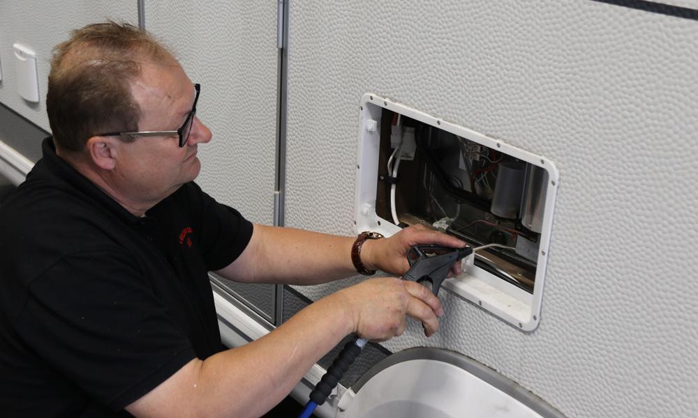 Støv og skitt i kjøleskapsregisteret reduserer virkningen, her blåser Espen det rent med trykkluft