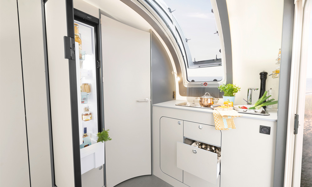 The kitchen is located at the front, where a large panoramic window in the front provides light and air